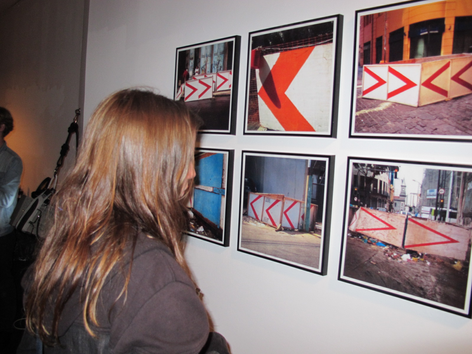 A guest looking at photographs by Raul Mourão