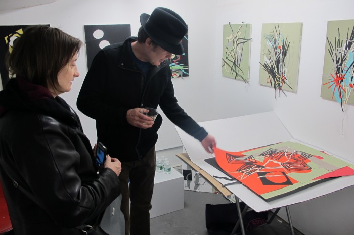 Writers Lori Ortiz and Jeffrey Cyphers viewing work in the artist's studio which was opened to visitors for the evening