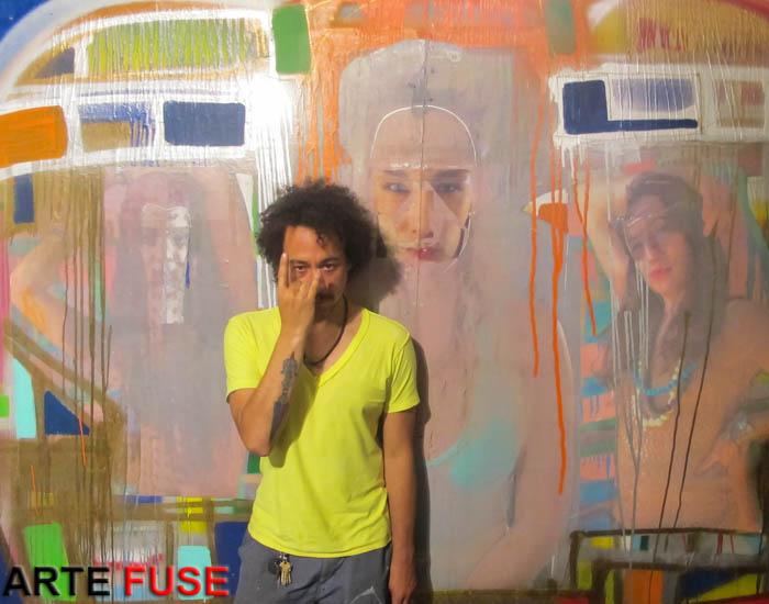 Artist Kimyon Huggins in front of his work