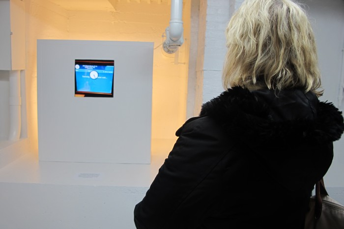 A guest enjoying the video at the opening of Monsters and Landscapes by Ryan Piers Williams