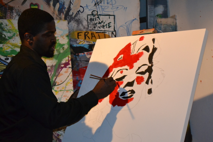 Artist Monel King Aliote working on the first segment of the painting