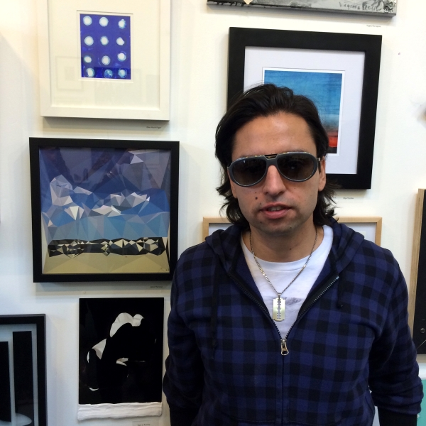 Artist and publisher of Arte Fuse Jamie Martinez next to his work