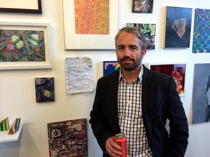 Artist William Powhida next to his work on opening night