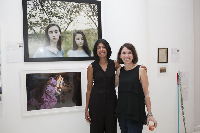 Manjari Sharma (artist) with Lydia Panas (artist) next to their donated prints.