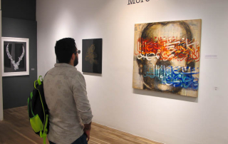 A guest enjoying the painting by Ayad Alkadhi.