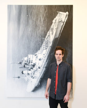 Artist Eric Helvie in front of his work.